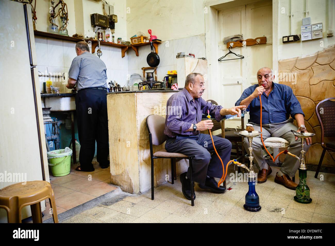 Gli uomini arabi in un caffè tradizionale fumatori tubazione acqua, Nazaret, Bassa Galilea regione, Israele. Immagini Stock