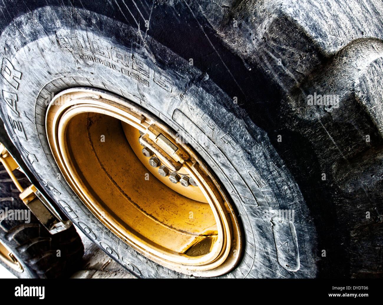 Primo piano del gigante di pneumatici e ruote di un bulldozer che mostra la sporcizia e usura del battistrada Immagini Stock