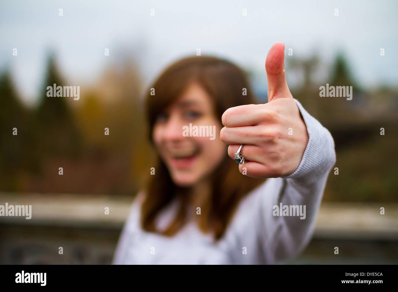 Bella ragazza facendo un pollice in alto segno con la mano e le dita per questa unica immagine di approvazione. Immagini Stock