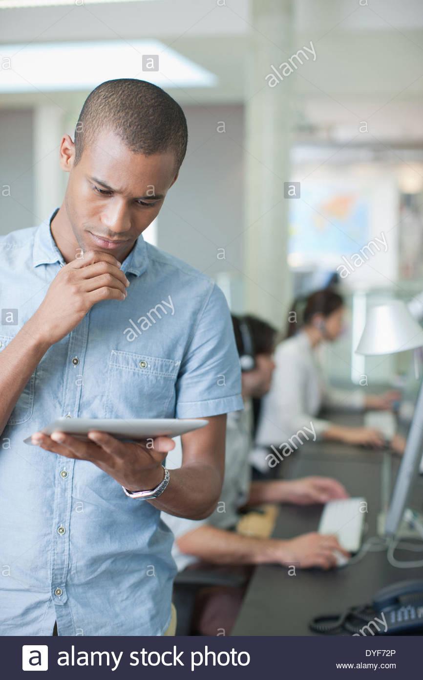 Uomo con tavoletta digitale in ufficio Immagini Stock