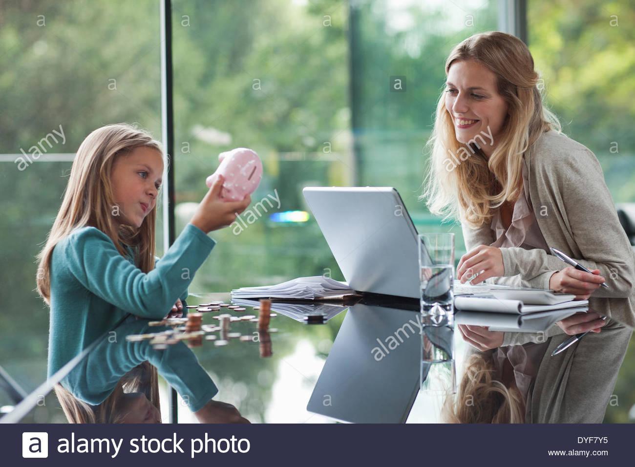 Madre guarda la figlia contare monete da salvadanaio Immagini Stock