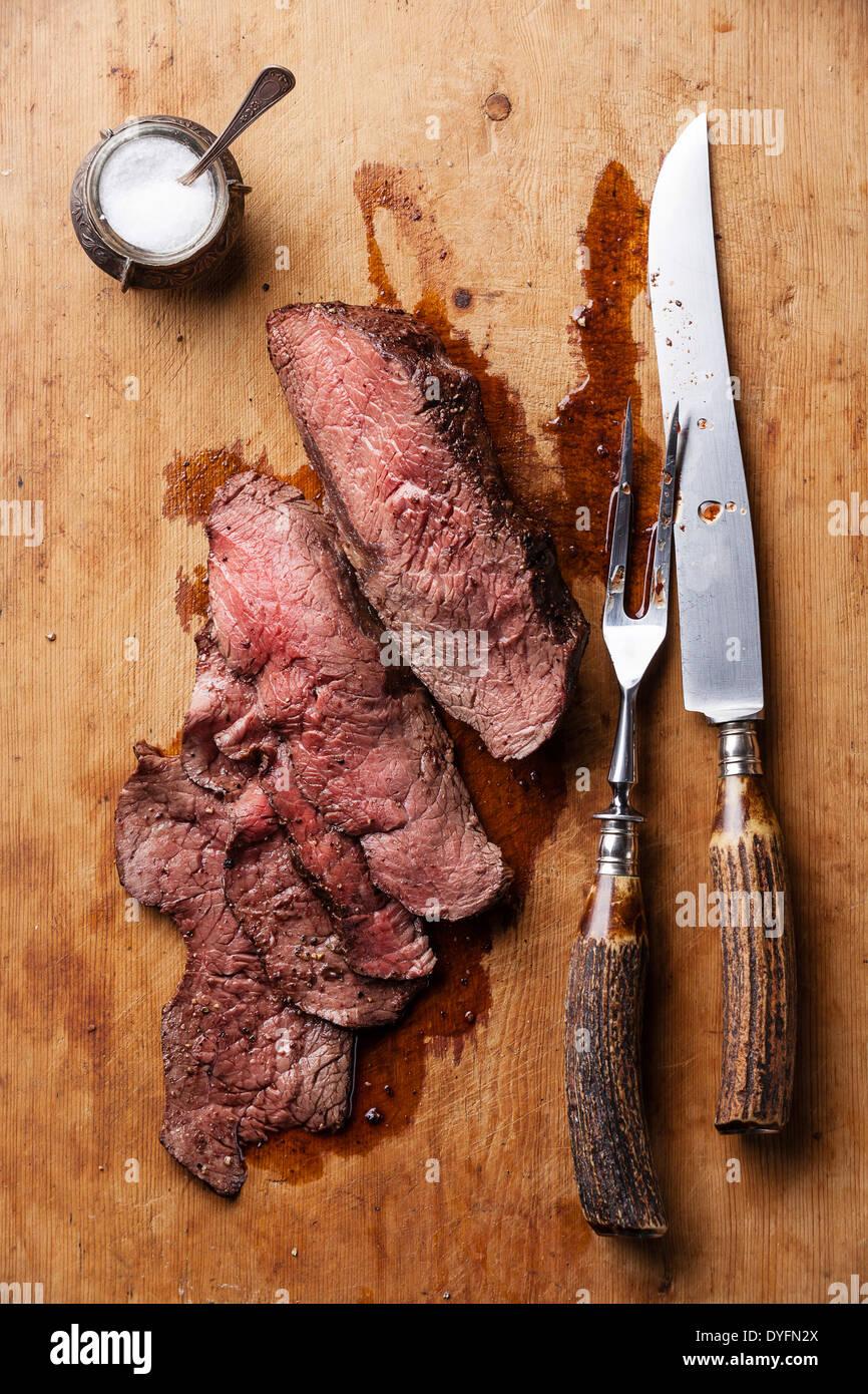 Arrosto di manzo con coltello e forchetta per la carne su sfondo di legno Immagini Stock