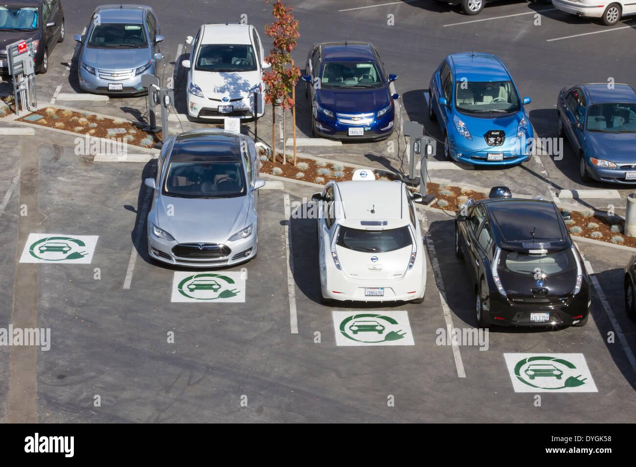 Diversi tipi di plug-in di auto elettriche parcheggiato a EV stazioni di carica in una società di parcheggio Immagini Stock