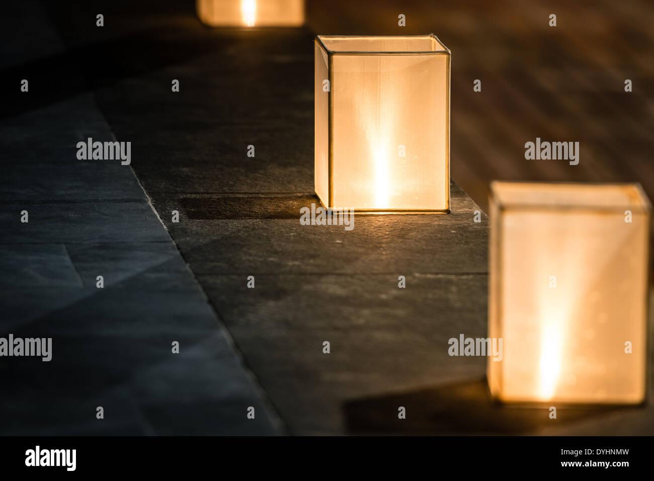 Fila di tre quadrati lanterne con luce fioca in piedi sul