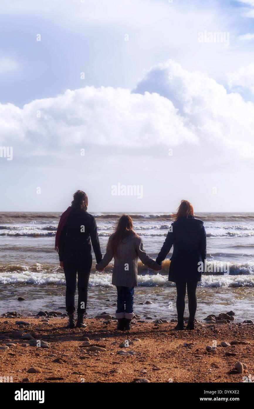 Le tre ragazze mano nella mano al mare Immagini Stock