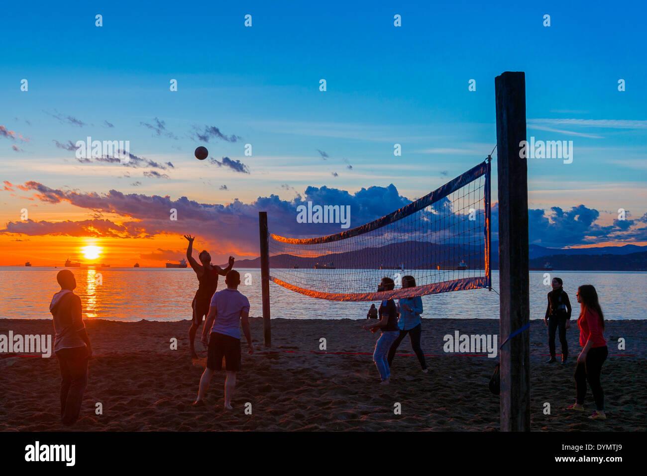 Una partita di beach volley in spiaggia al tramonto, English Bay Beach, Vancouver, British Columbia, Canada Immagini Stock