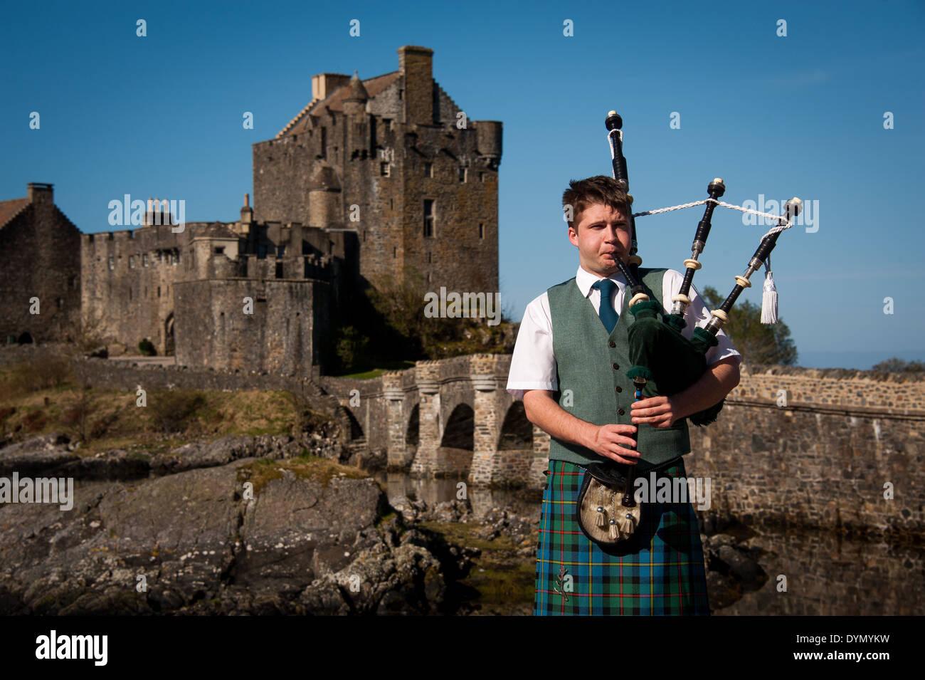 Cornamuse player con Castello Eilean Donan in background, Scotland, Regno Unito Foto Stock