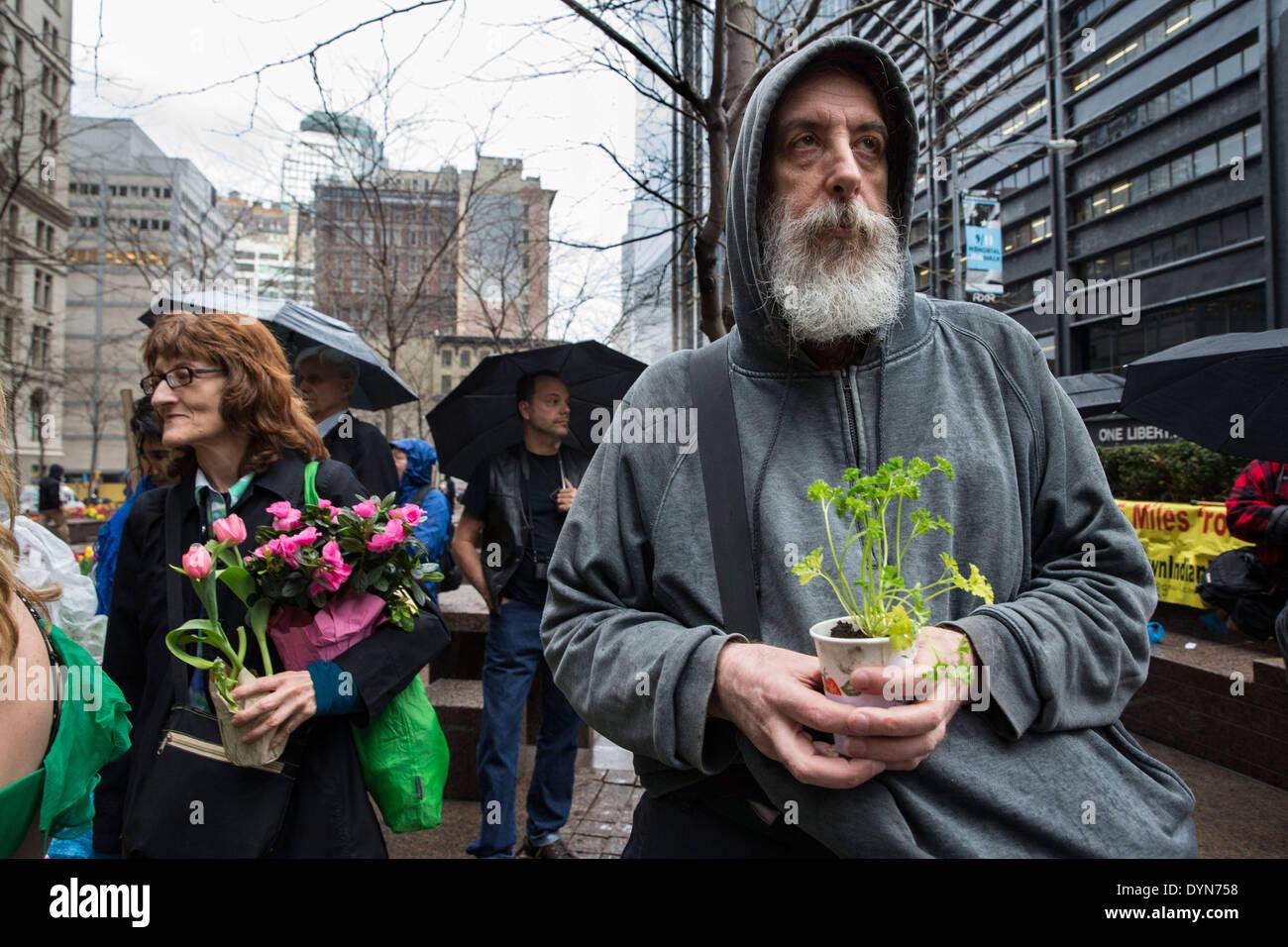New York, Stati Uniti d'America. Il 22 aprile 2014. Gli attivisti ambientali assistere ad una manifestazione di protesta in Zuccotti Park sulla Giornata della Terra. I manifestanti hanno portato alle piante e cantati ' sistema non modifica il cambiamento climatico, ' tenendo mirano a grandi aziende che non aderiscono alle preoccupazioni per l'ambiente. Questi manifestanti hanno anche espresso che capatilisim sfruttamento della natura è il rovescio della medaglia per lo sfruttamento del lavoro umano. Credito: Scott Houston/Alamy Live News Immagini Stock