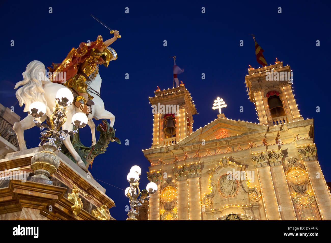 Statua di San Giorgio che uccide il drago montato su un piedistallo durante la città festa della Basilica di San Giorgio a Gozo a Malta. Immagini Stock