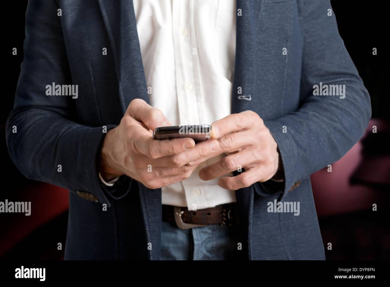 Casual uomo d affari l'invio di un messaggio di testo su un telefono cellulare in uno sfondo scuro Immagini Stock