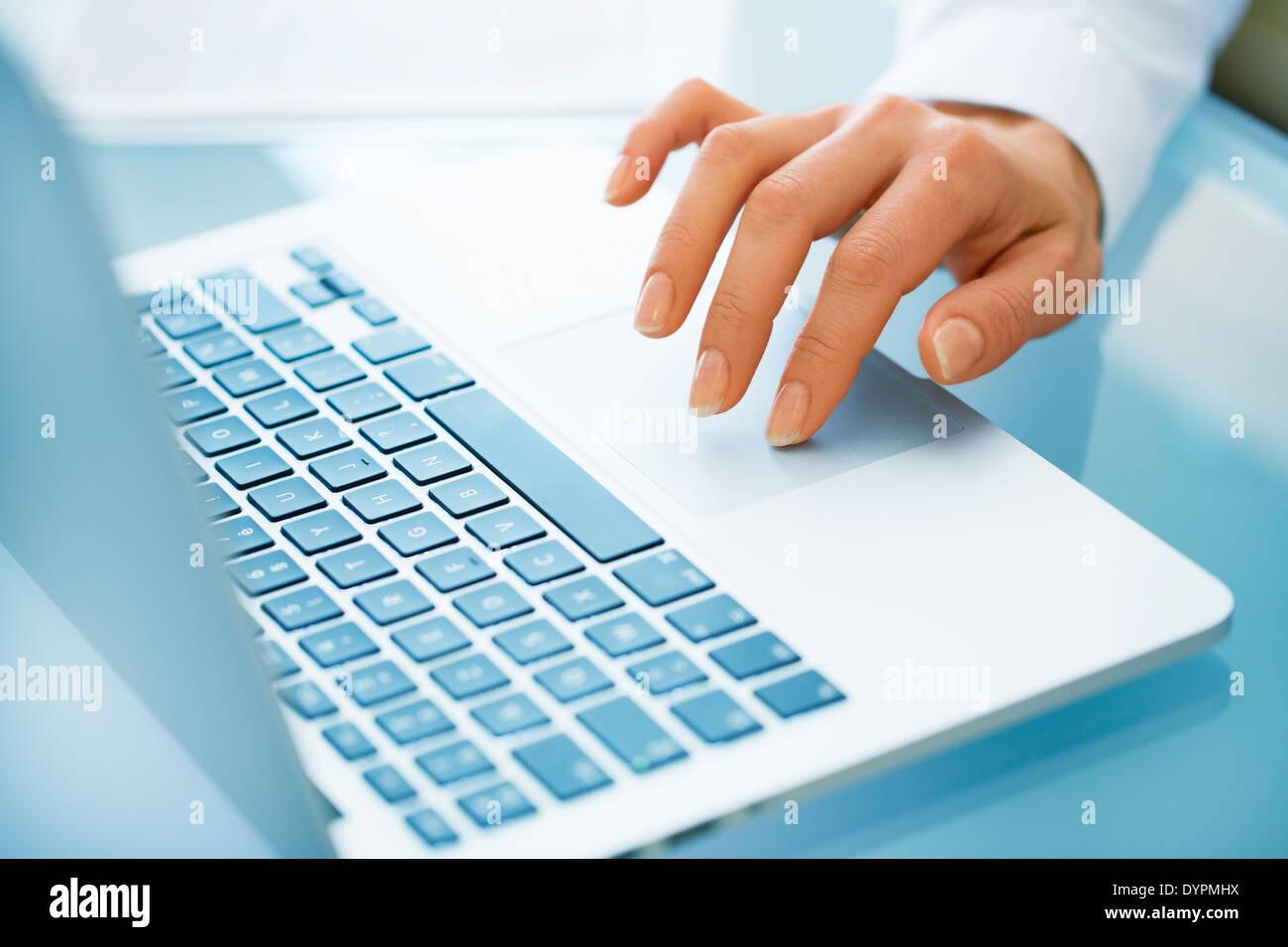 Close-up di mano Donna che utilizza un computer portatile Immagini Stock