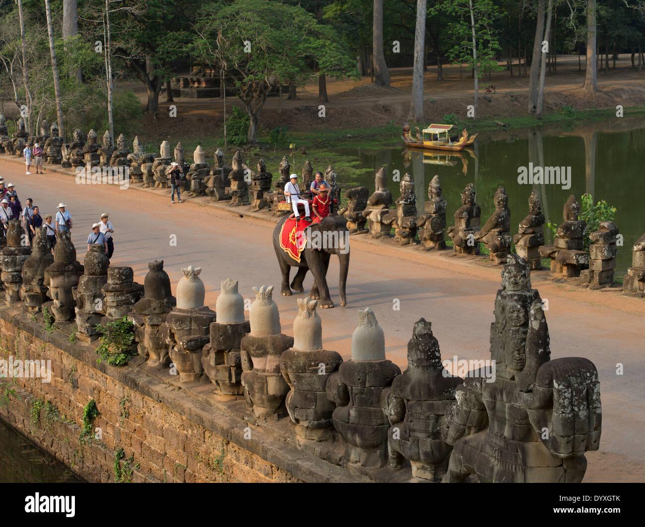 I turisti a cavallo di un elefante che si avvicinano alla porta sud di Angkor Thom, Siem Reap, Cambogia Immagini Stock