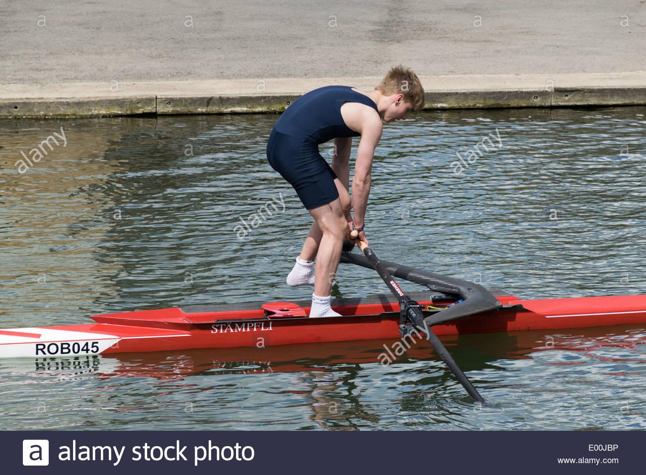Un vogatore tenta di stare in piedi su una gamba in una unica sede scull barca sul fiume Cam in Cambridge Immagini Stock