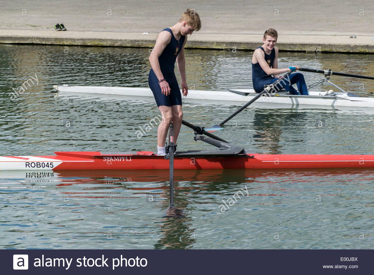 Un vogatore tenta di alzarsi in piedi in un unico sedile scull barca sul fiume Cam in Cambridge mentre un altro vogatore guarda su Immagini Stock