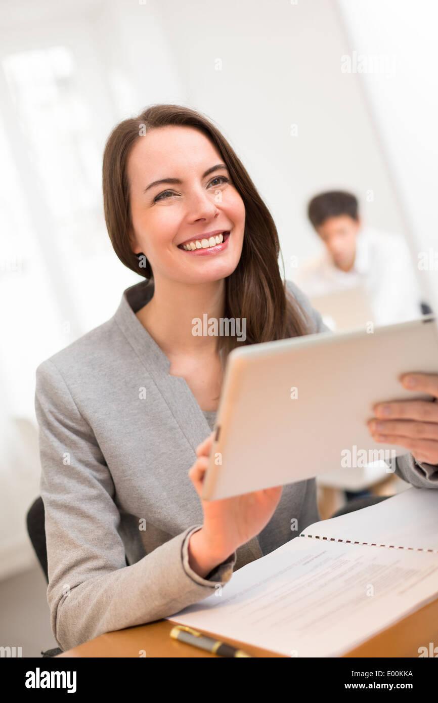 Carino Donna sorridente desk digitale compressa web surfing Immagini Stock