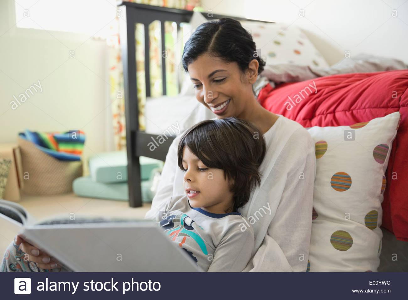 Madre e figlio libro di lettura in camera da letto Immagini Stock
