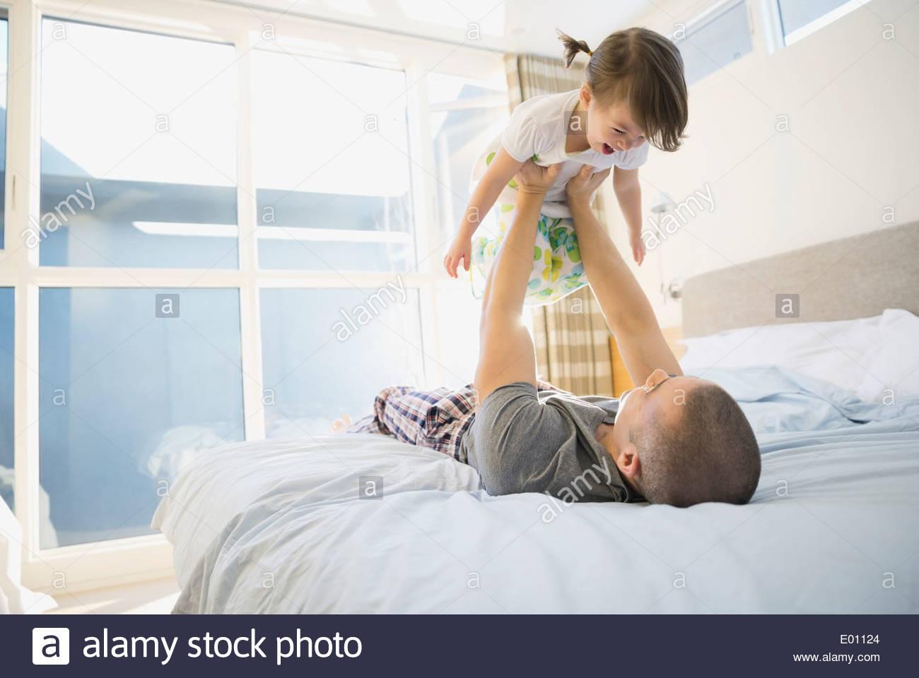 Padre figlia di sollevamento overhead sul letto Immagini Stock