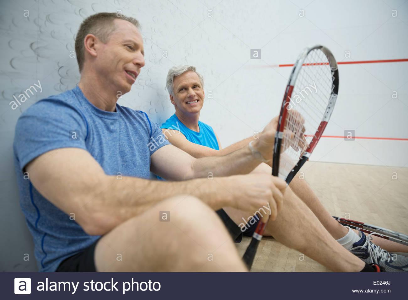 Gli uomini a parlare sul campo da squash Immagini Stock