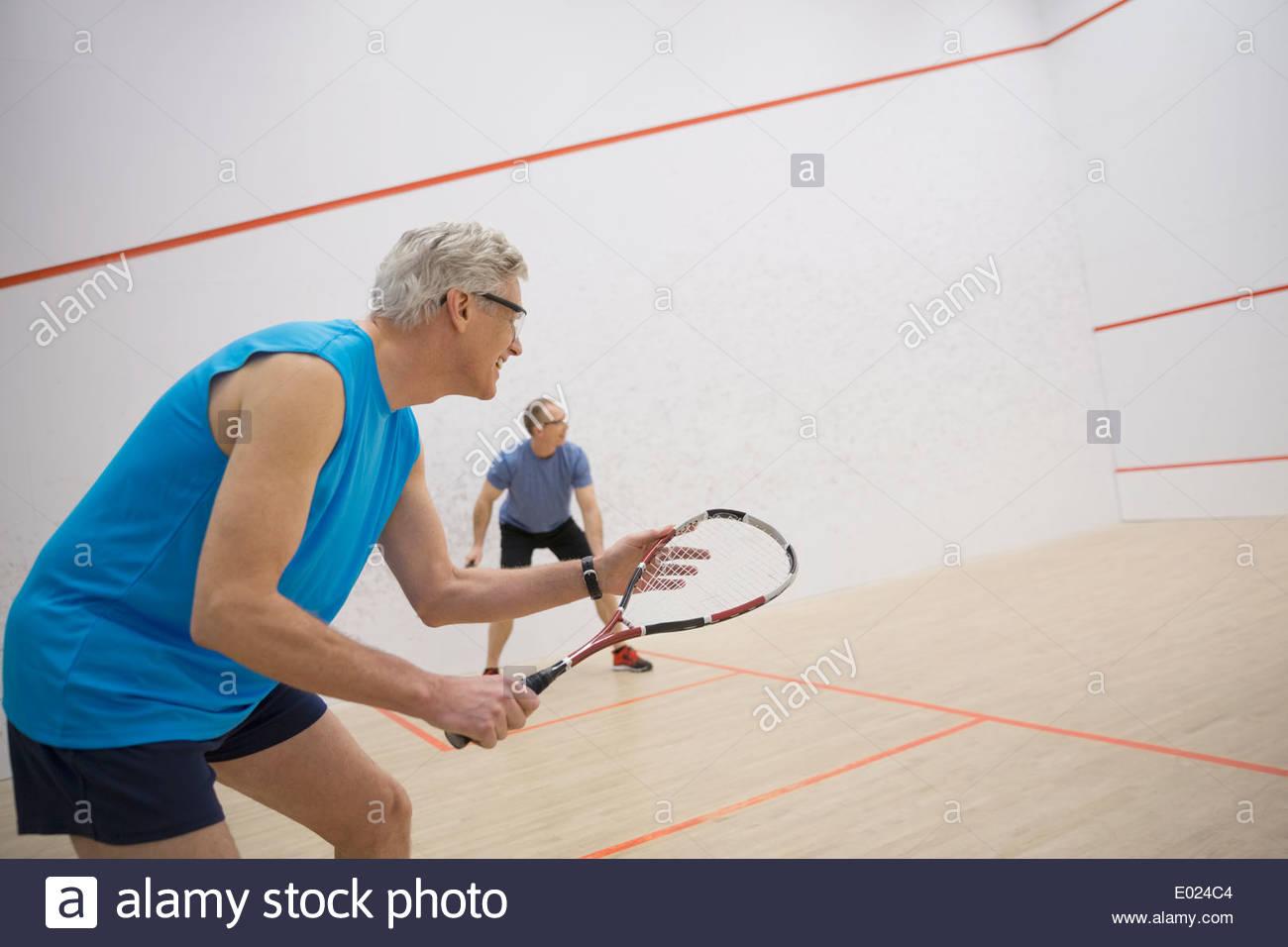 Gli uomini a giocare a squash su corte Immagini Stock