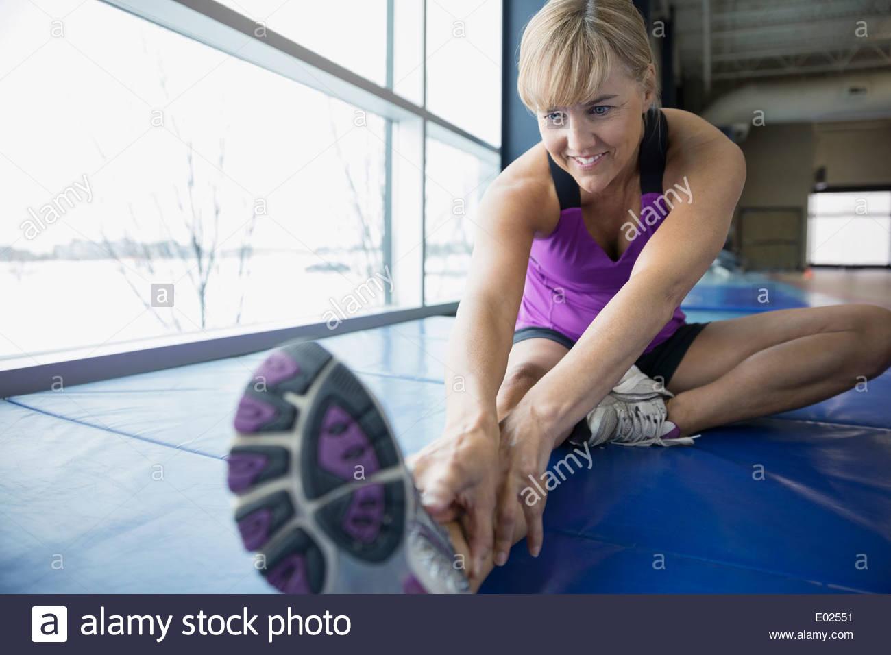 Donna stretching gamba alla palestra Immagini Stock