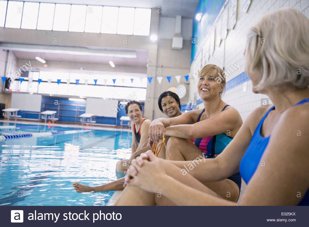 Le donne parlando a piscina interna Immagini Stock