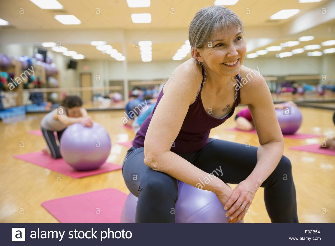 Donna sorridente al fitness palla in classe di esercizio Immagini Stock