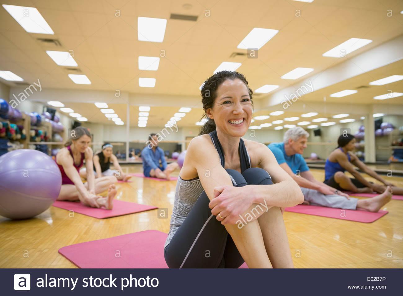 Donna sorridente sul materassino yoga nella classe di esercizio Immagini Stock