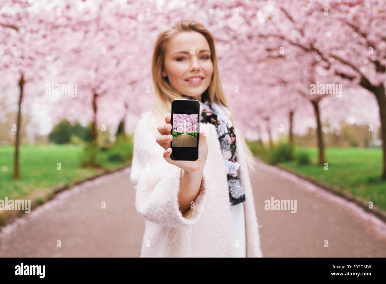 Piuttosto giovane donna mostra un'immagine della molla blossom garden mentre si sta in piedi in un parco. Caucasian giovani femmine che mostra la molla park Immagini Stock