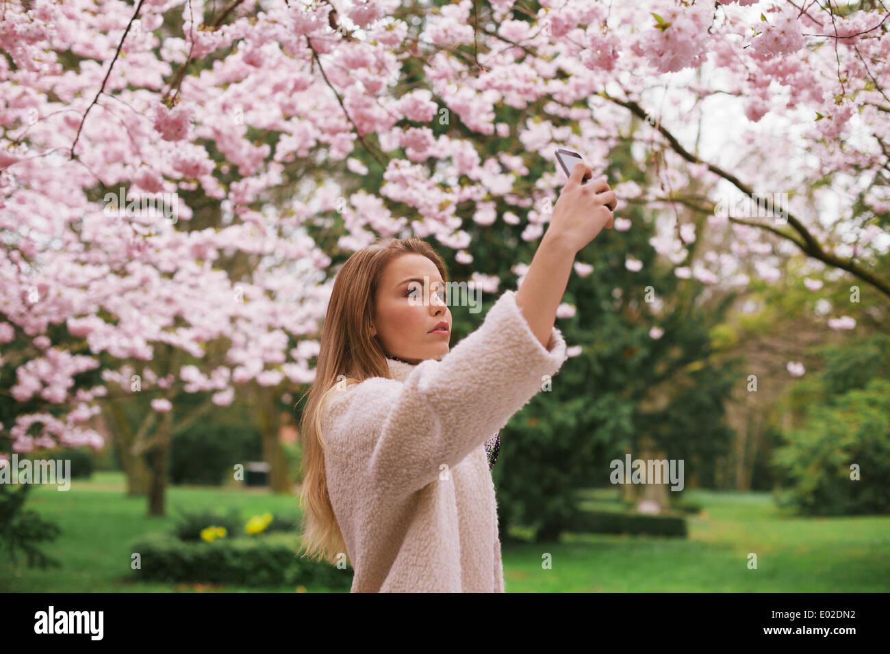 Giovane donna caucasica dipinge sbocciare fiori con il suo telefono cellulare. Donna attraente fotografare fiori presso il Parco di primavera Immagini Stock