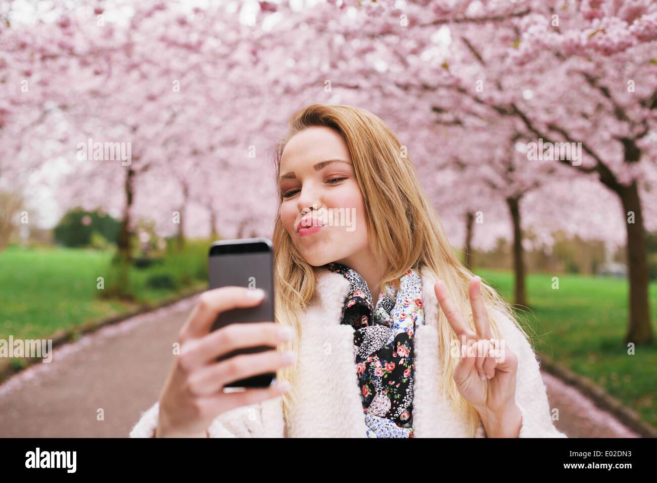 Attraente giovane donna in posa per selfie. Bellissima femmina a molla blossom park tenendo autoritratto con il telefono cellulare. Immagini Stock