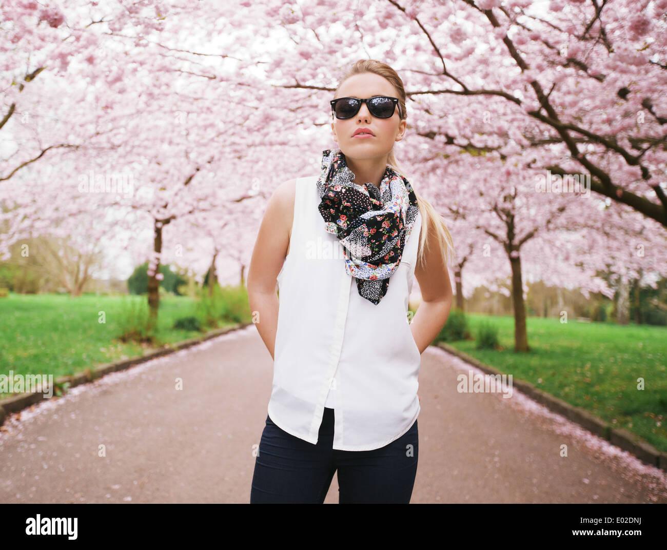 Moda giovane donna in posa con fiducia al parco. Attraente modello femminile a primavera sbocciano i fiori park Immagini Stock