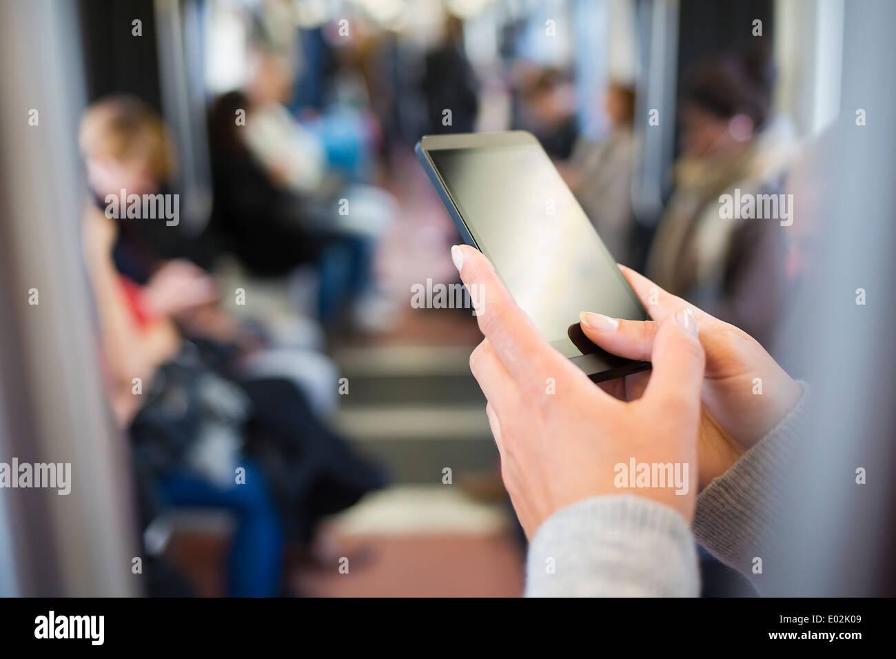 Femmina cellulare a mano della metropolitana sms messaggi e-mail Immagini Stock