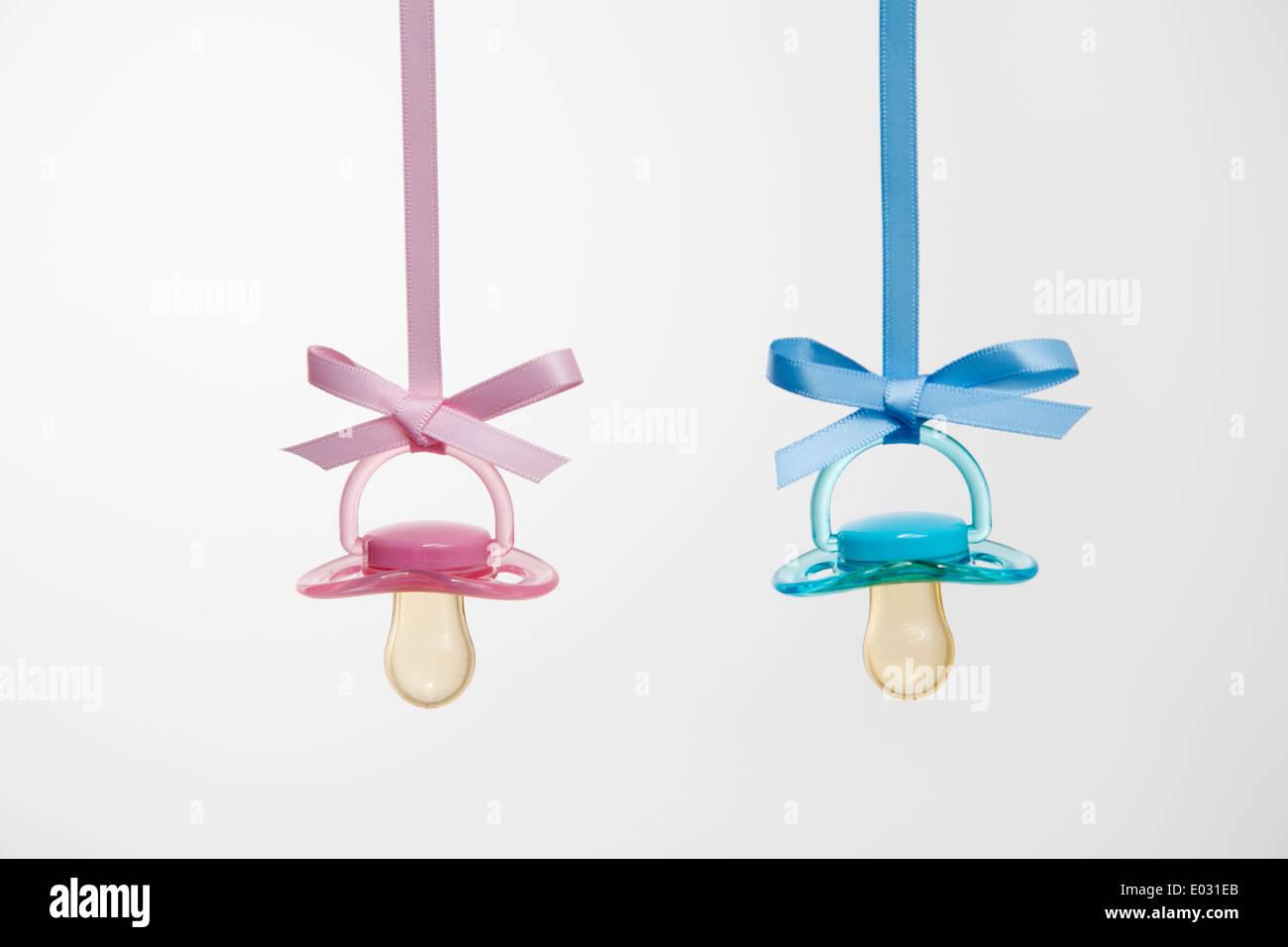 I succhietti per neonati appesi da nastri contro uno sfondo semplice. Immagini Stock