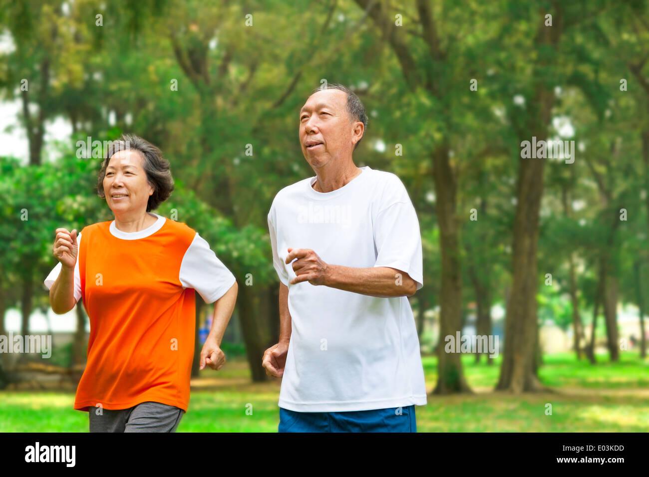 Felice coppia senior correndo insieme nel parco Immagini Stock