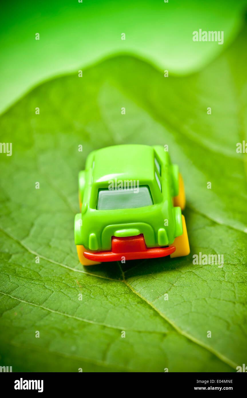 Piccolo verde giocattolo auto su una foglia verde auto concept Immagini Stock