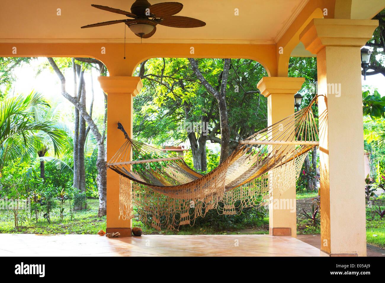 Un invitante amaca appesa su un soleggiato portico con i tropici in background. Immagini Stock