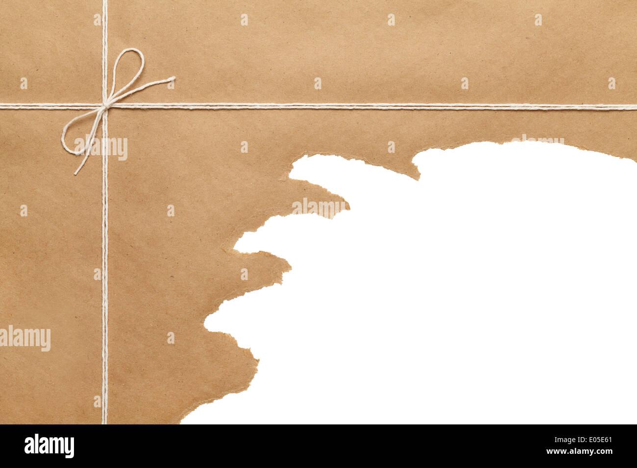 Carta marrone pacchetto legato con corda sottile stringa bow strappato aperto su sfondo bianco spazio copia. Foto Stock