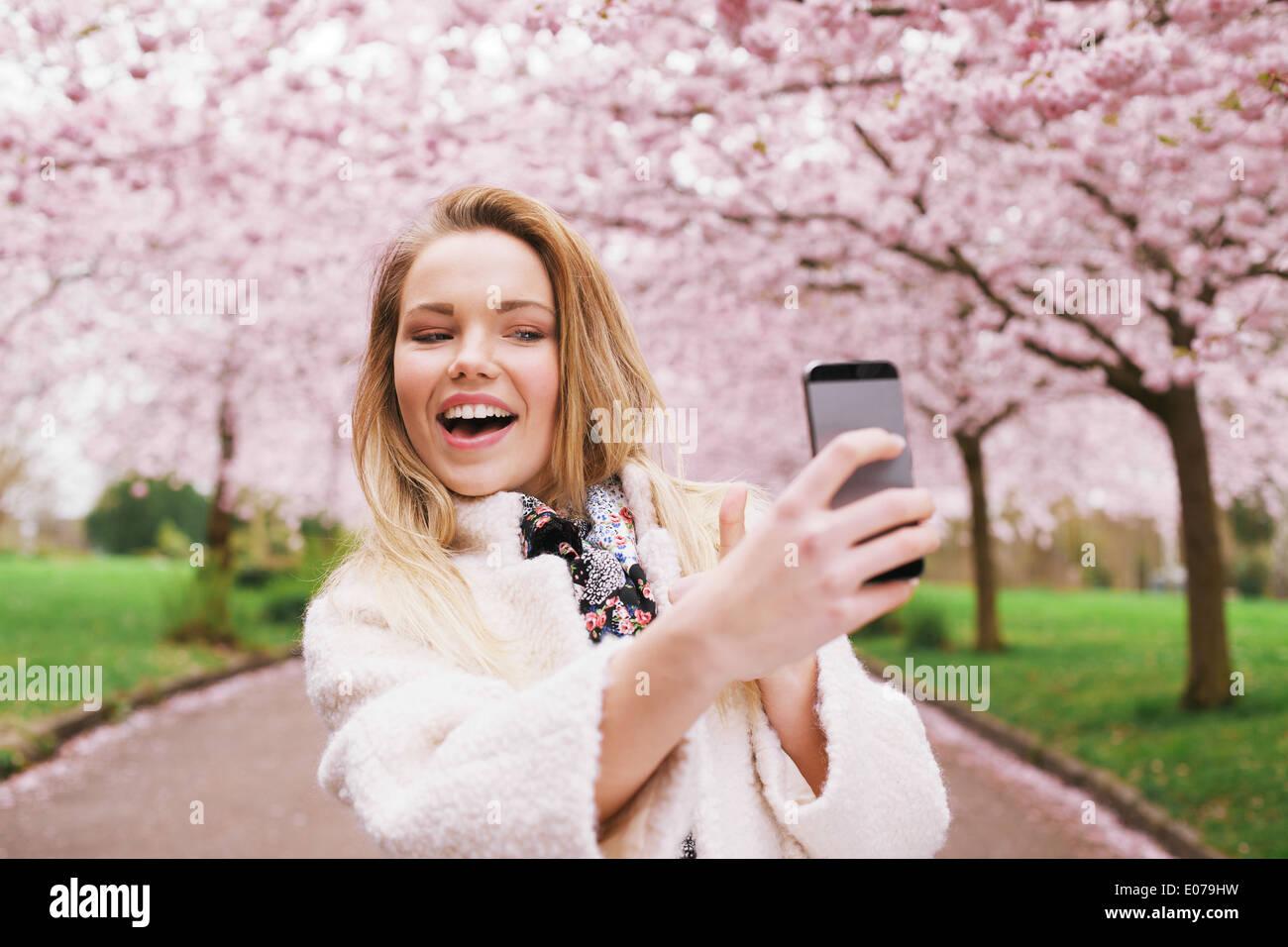 Felice Giovane Donna Fotografa se stessa utilizzando il suo telefono cellulare. Femmina caucasica selfie parlando con il suo smart phone al parco. Immagini Stock