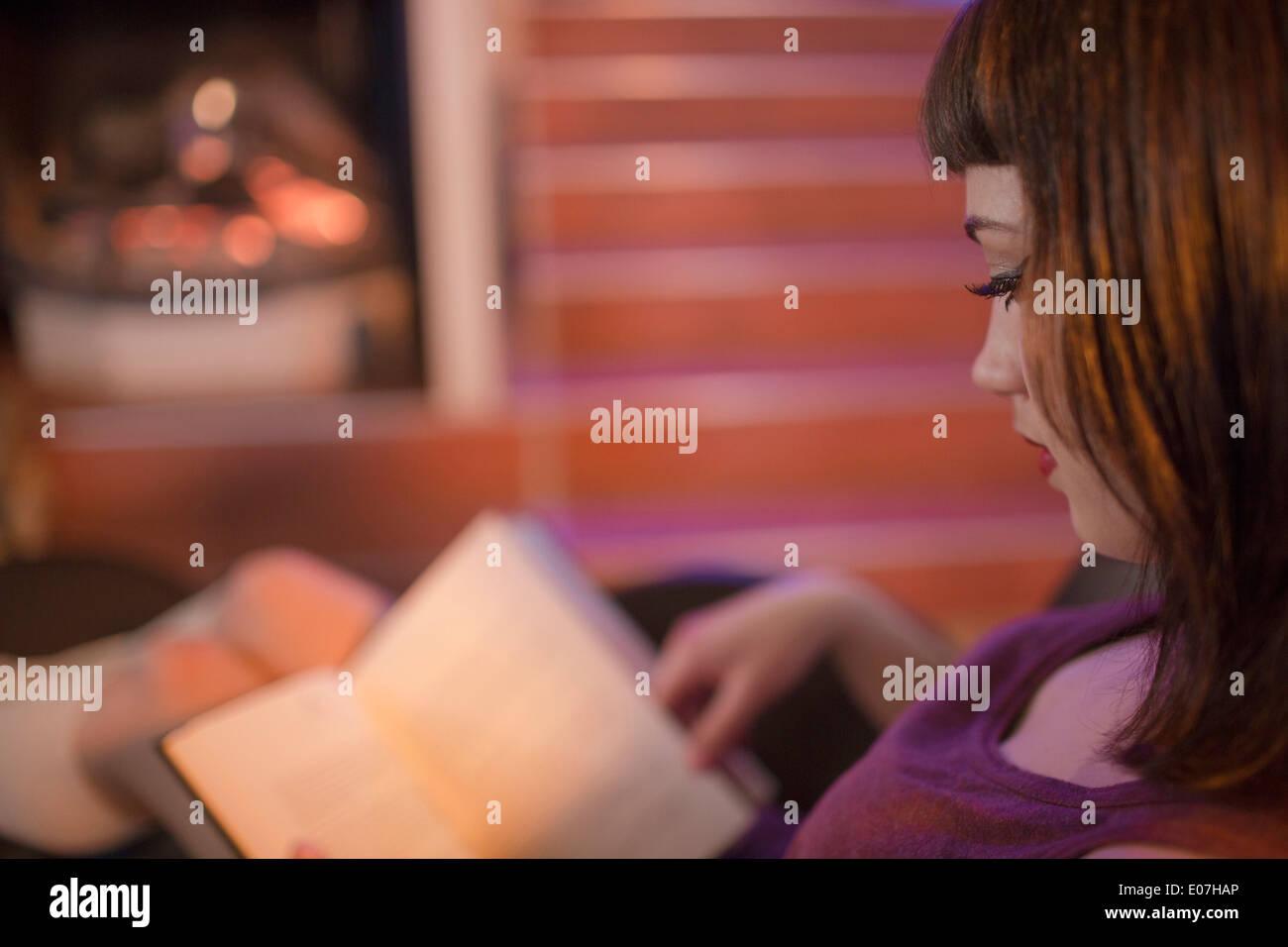 Giovane donna la lettura di un libro, vista laterale Immagini Stock