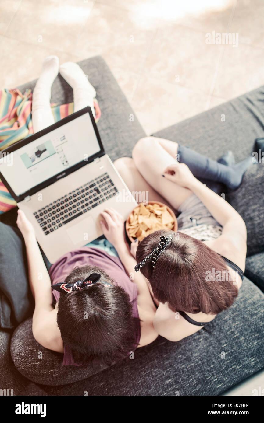 Due giovani donne navigano in internet mentre avente uno snack Immagini Stock