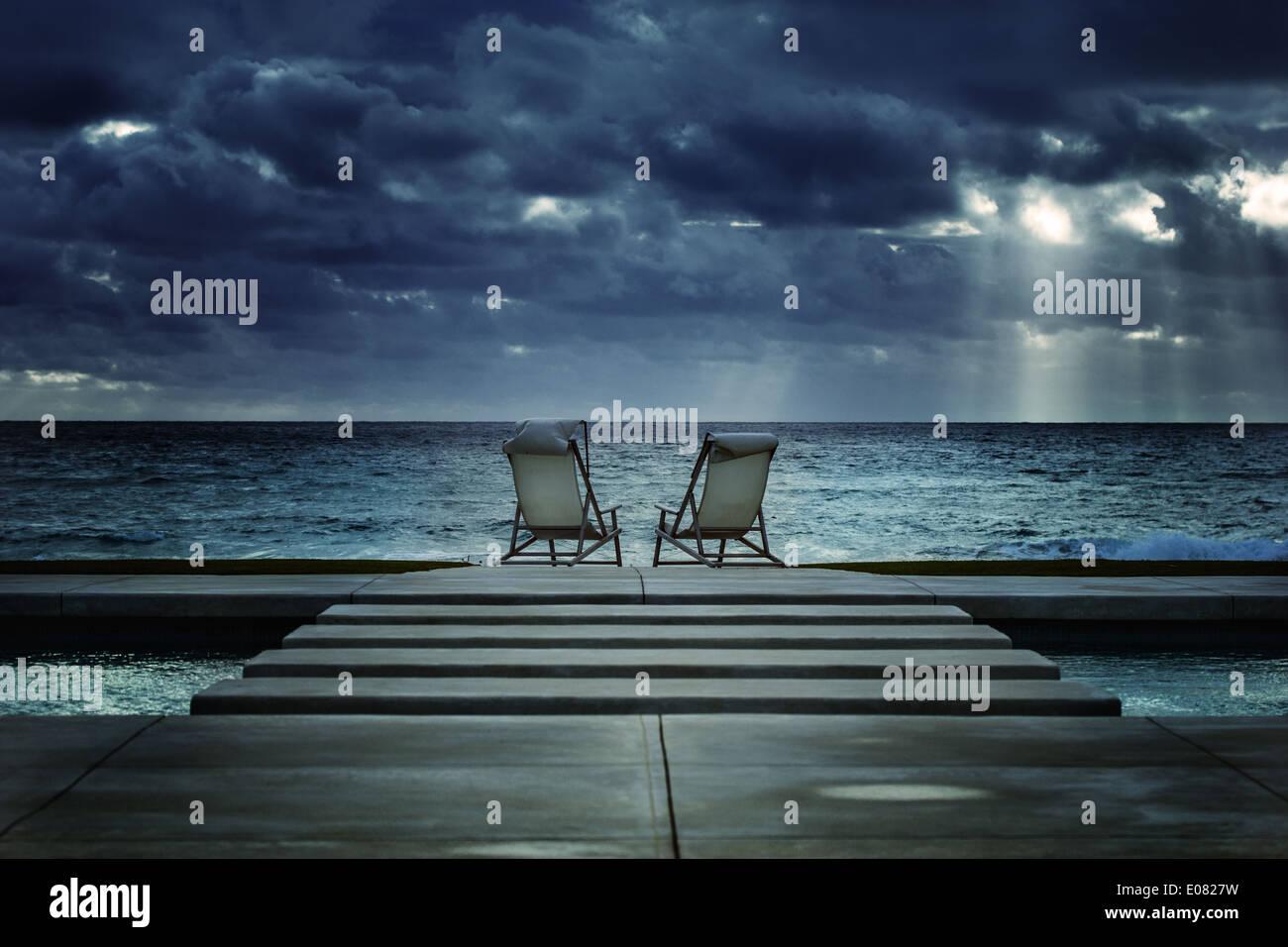 Una vista di due comode sedie a sdraio sulla spiaggia di Palm Island con vista sull'Oceano Atlantico Foto Stock