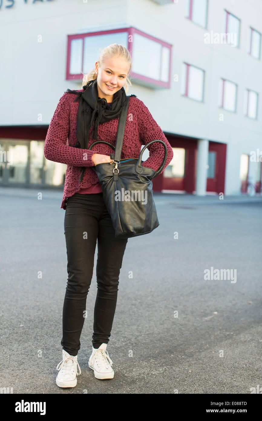 A piena lunghezza Ritratto di felice ragazza adolescente con borsa a tracolla su high school campus Immagini Stock