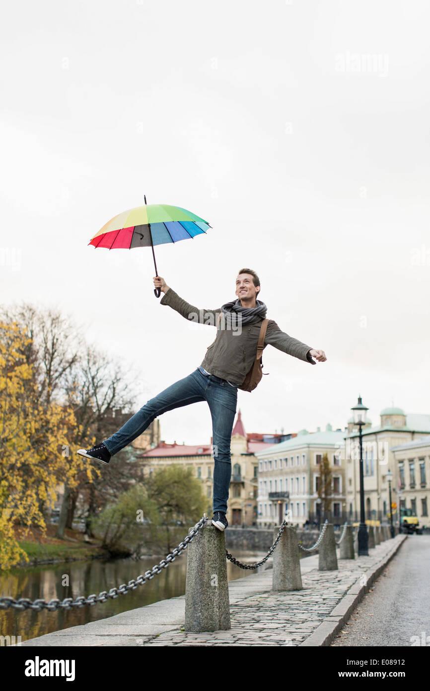 Lunghezza completa di imprenditore con ombrellone in equilibrio su bollard all'aperto Immagini Stock