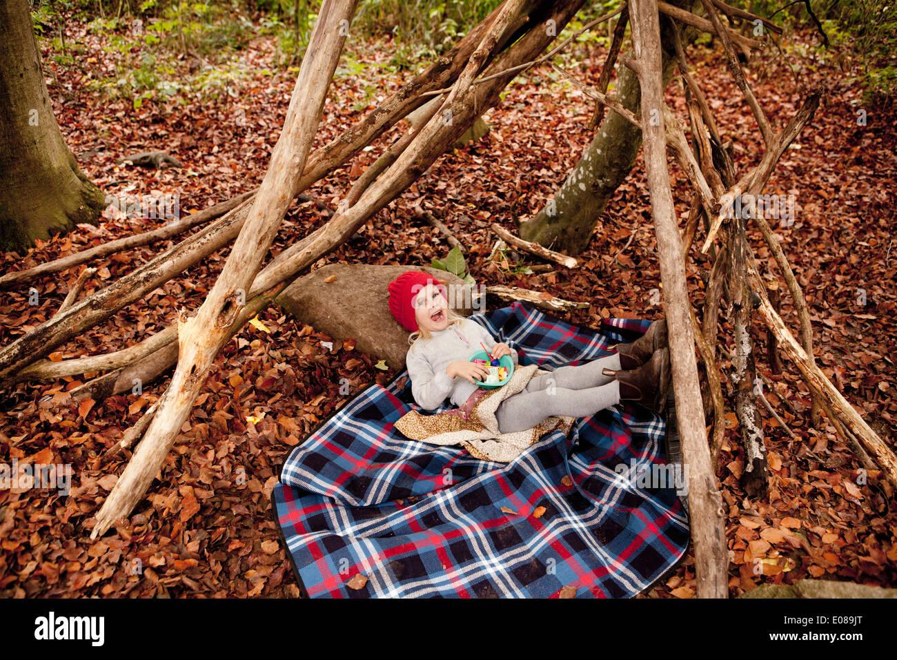 A piena lunghezza Ritratto di ragazza distesa sulla coperta picnic in foresta Immagini Stock