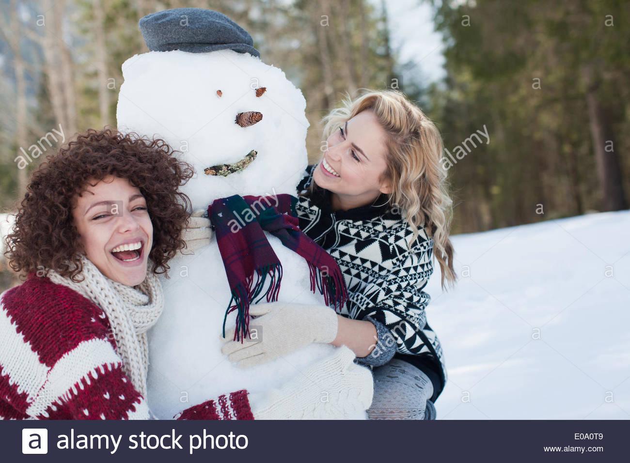 Due donne abbracciando pupazzo di neve Immagini Stock