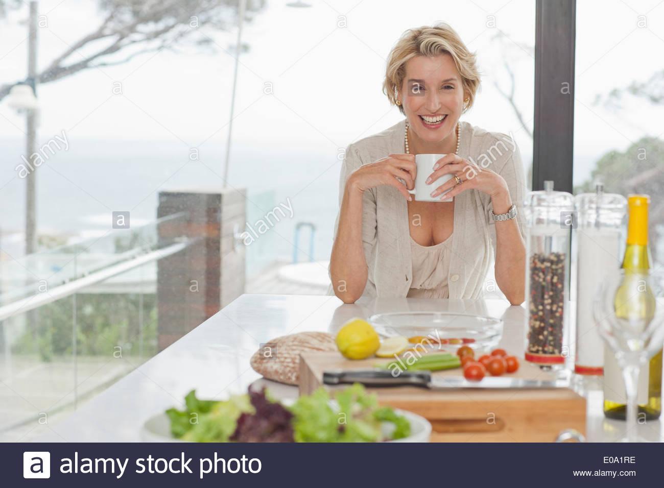 Donna di bere il caffè in cucina Immagini Stock