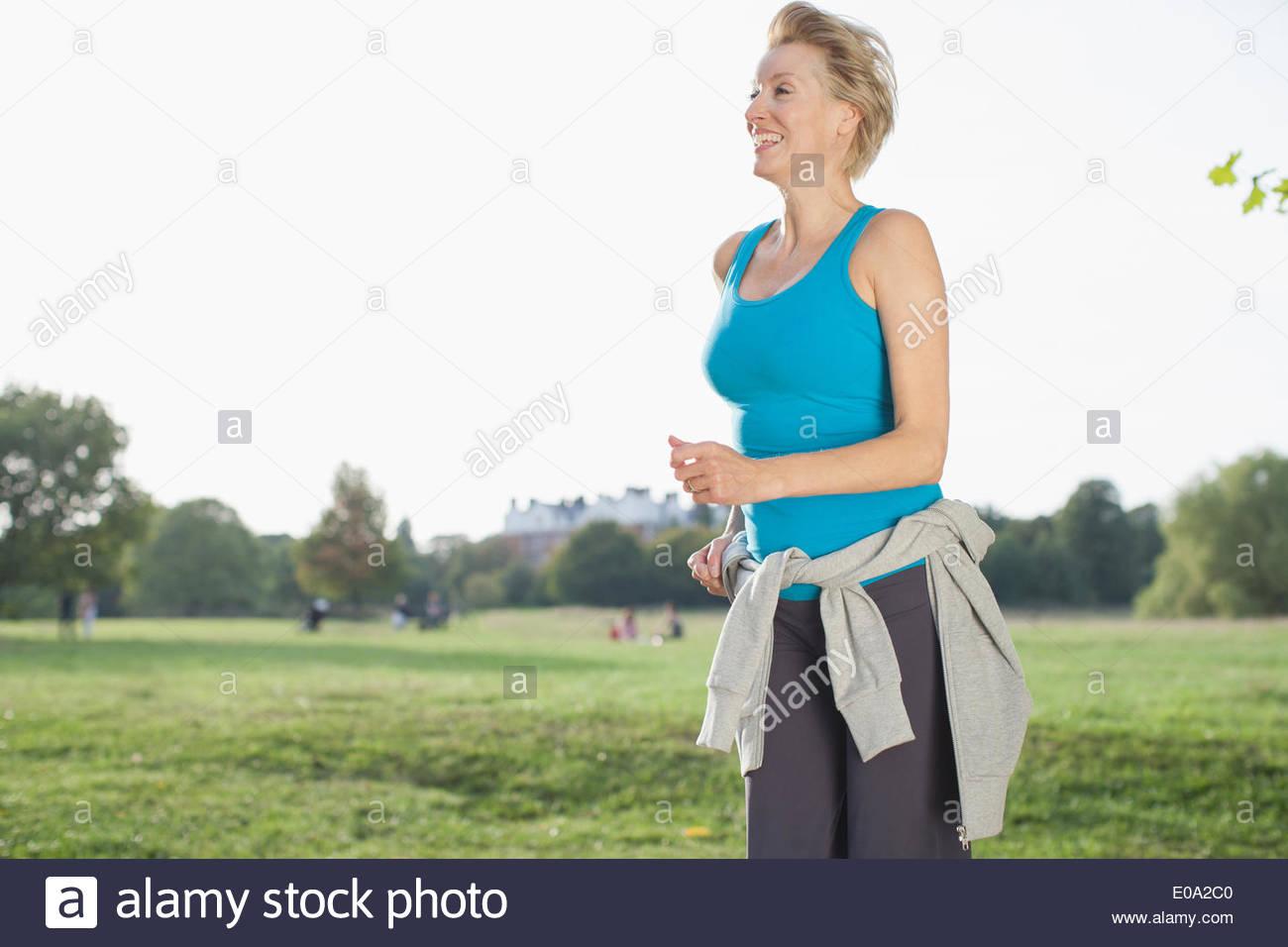 Donna sorridente a fare jogging nel parco Immagini Stock