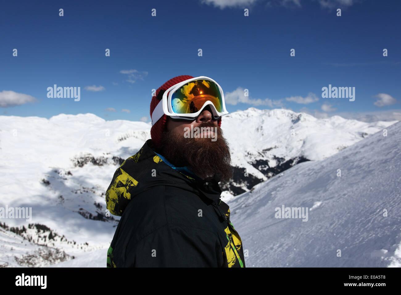 Metà uomo adulto sciatore cercando fino alla montagna, Mayrhofen, Tirolo, Austria Immagini Stock