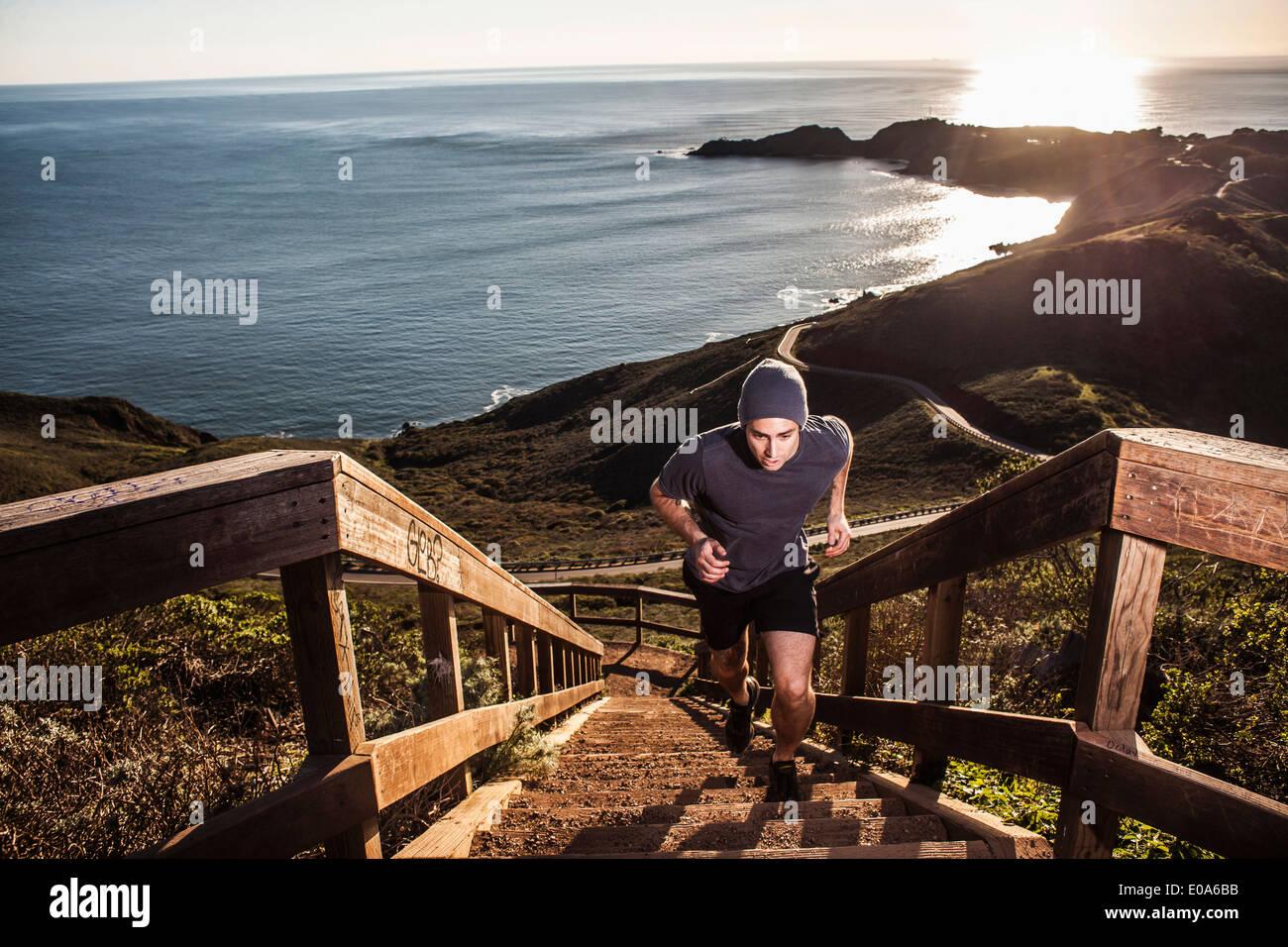 Giovane uomo in esecuzione su scala costiera al tramonto Immagini Stock