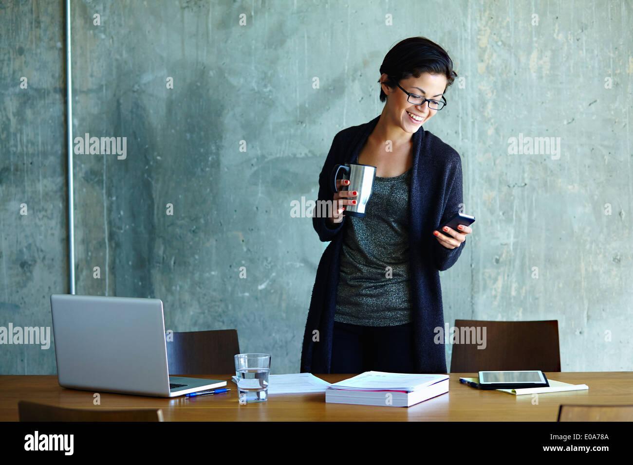 Giovane imprenditrice guardando smartphone in ufficio Immagini Stock